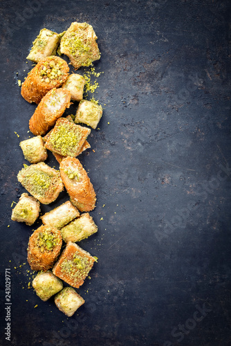 Photo Traditional Oriental baklava collection as top view on a black board with copy s
