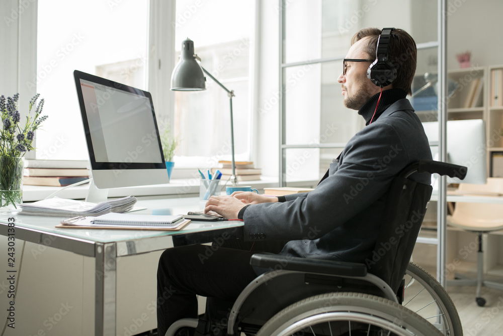 Fototapety, obrazy: Disabled businessman in wheelchair wearing headphones and concentrated on his work, he typing on keyboard and looking at computer screen