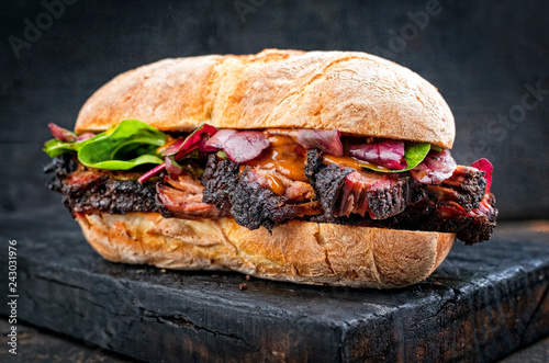 Traditional barbecue pulled pork piece of Bosten butt as sandwich with lettuce as closeup on a black board