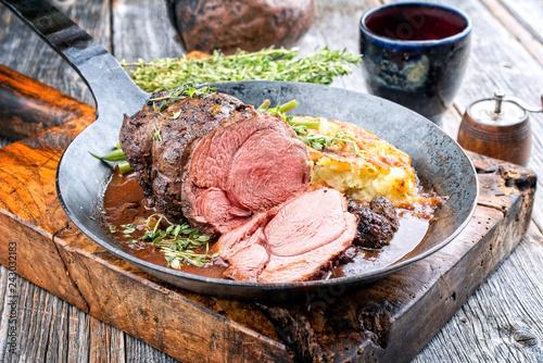 Gegrillter Wildschwein Braten mit schweizer Rösti in Wildsauce mit Rotwein als closeup in einer schmiedeeisernen Pfanne