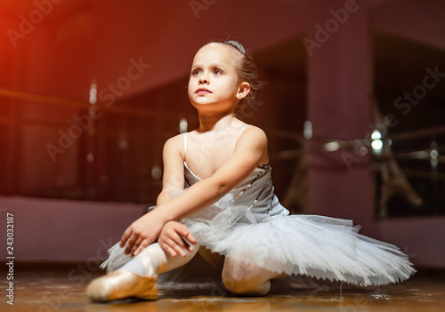 Little ballerina in white tutu sitting on floor and resting in dance studio Tapéta, Fotótapéta