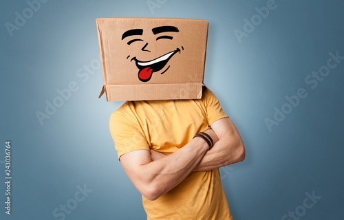 Foto Young boy standing and gesturing with a cardboard box on his head