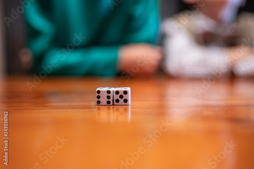 фотография  Gaming dice on the table with kids outlines in the background.