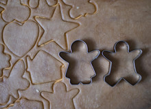 Iron Cookie Molds In The Form Of A Boy And A Girl Stand On A Chocolate Rolled Out Dough; Heart, House, Stars, Clover Are Carved On The Dough (horizontally And Close Up)