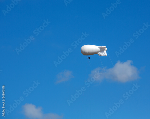 Large white air balloon in the shape of an airship with camera on the background of blue sky