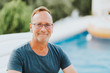 canvas print picture - Outdoor portrait of 50 year old man resty by the pool, wearing blue t-shirt and glasses