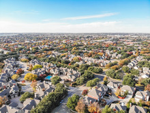 Top View Residential Subdivision In Fall Season With Colorful Autumn Leaves Near Dallas, Texas. Urban Sprawl Of Residential Houses And Apartment Building Complex, Blue Sky