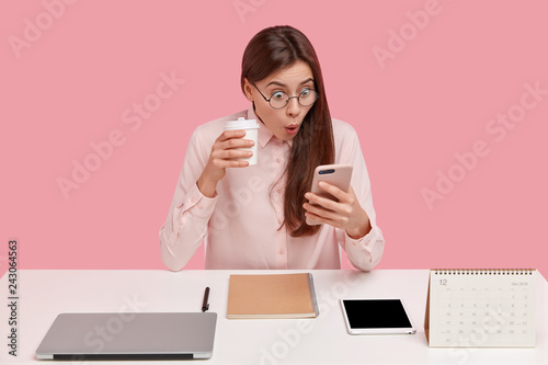 Photo of attractive young woman reads shocking news on mobile phone, watches video in social networks, drinks coffee from disposable cup, being office perfectionist, uses electronic gadgets Canvas Print