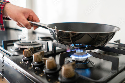 Stampa su Tela A man cooks in a frying pan, puts it on the stove