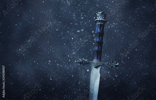 Photographie mysterious and magical photo of silver sword over gothic snowy black background