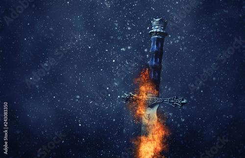mysterious and magical photo of silver sword with fire flames over gothic snowy black background Fototapeta