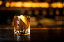 Glass Of A Rusty Nail Cocktail With Orange Zest On The Wooden Bar Counter