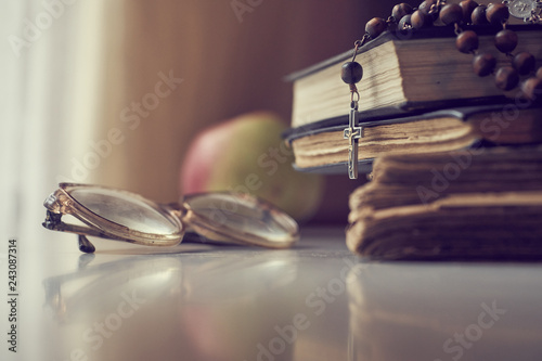 Fotografie, Obraz  The rosary beads on Catholic Church liturgy books and old glasses and ripe apple on the side of them