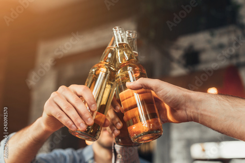 Fotografía  Men clinking bottles of beer together in bar