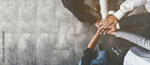 Business people putting their hands together, top view