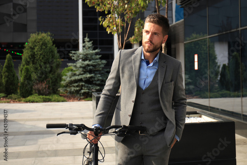 Valokuva  Confident young businessman standing with bicycle on the street in town