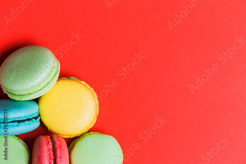 Fotobehang Dessert Closeup of red background for copy space with colorful macaroons in the corner.