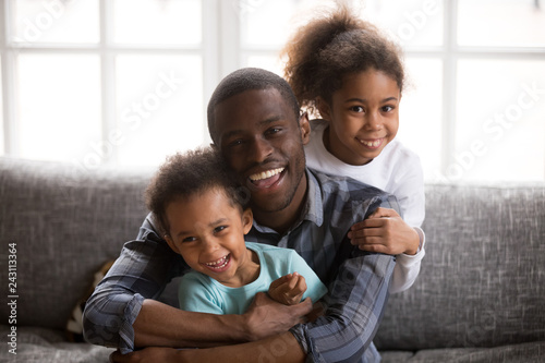 Happy african american dad and mixed race children, cheerful black family daddy embracing little son daughter sitting on sofa at home looking at camera, loving single parent with 2 cute kids portrait