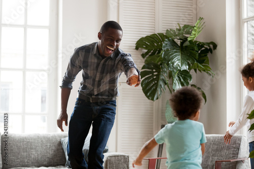 Happy african american dad laughing running in living room