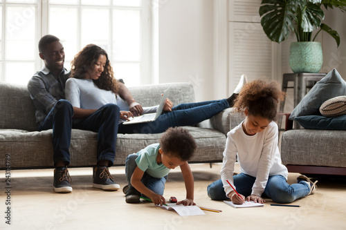 Black family relaxing at modern home, african american ...
