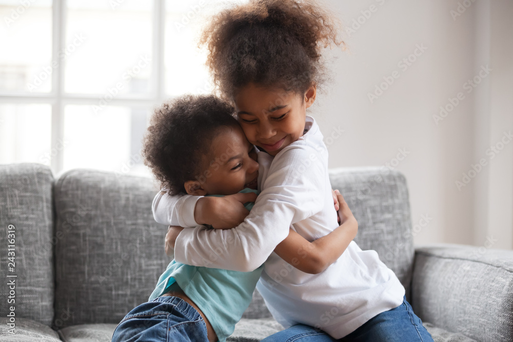 Fototapety, obrazy: Cute happy african american siblings hugging cuddling feeling love and connection, smiling mixed race kid girl sister embracing little boy brother sitting on couch, 2 children good relationships