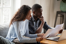 Serious Worried African American Couple Reading Documents Consider Mortgage Loan Insurance Contract Terms, Focused Black Man And Woman Holding Checking Bank Papers At Home, Domestic Bills Concept