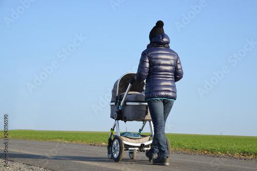 Fotografia, Obraz  Walking woman with baby stroller in sunny day.
