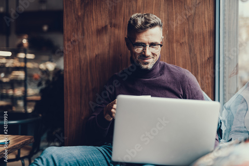 Man looking on netbook monitor and smiling