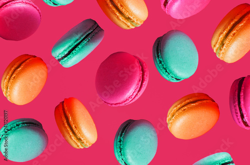 French colorful macarons background. Different types of macaroons in motion falling on a pink background