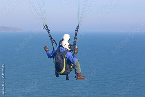 Tandem paraglider above the sea