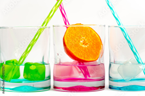 Fotografía  On a white background glasses in rainbow colors with colored ice, and cold water