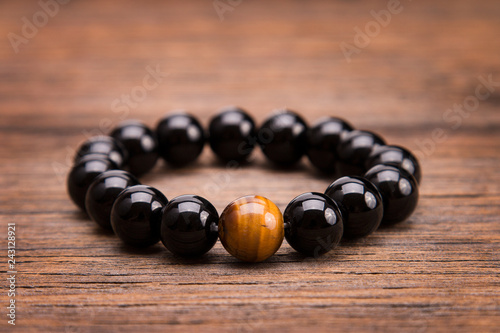 Tela Bracelet from round black stones lying on a wooden background.