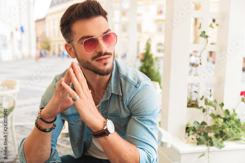 Fotomural  curious casual man wearing red sunglasses holding palms together