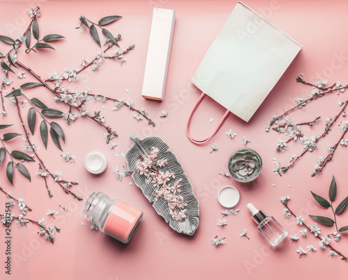 Cosmetic concept. Various facial products and paper shopping bag on pastel pink background with cherry blossom and leaves, top view, frame. Copy space for your design. Beauty blog layout. Flat lay
