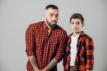 Man And His Little With Scared Faces Looking At The Camera. Close Up Photo. Isolated Grey Background. Excited Father And Son Have Seen Something Unusual And Interesting