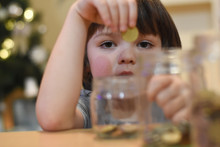 Boy Putting Coins In A Glass Jar. Concept Of Saving. Child Save Money For Christmas Presents