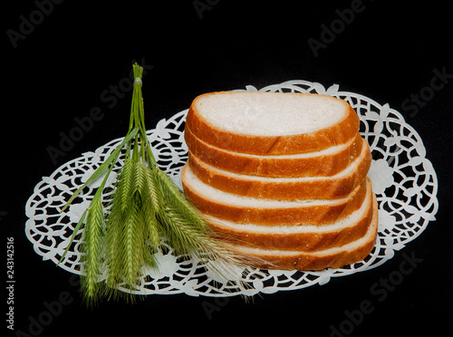 Fotografie, Obraz  Sliced Long loaf of bread, decorated with wheat spikes on black background