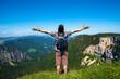 Man enjoying the Great Outdoors - hiker raising arms over blue sky