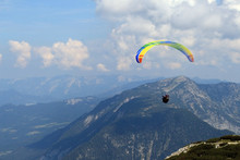 Paraglider Over The Tops Of The Mountains In Summer Sunny Day.