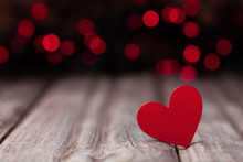 Red Wooden Heart Against Bokeh Background For Valentines Day Card.