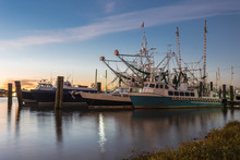 Large Shrimping Boats Waiting To Go To Work As Sun Sets In Distance