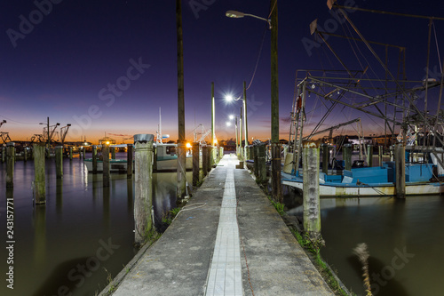 Photo Old vintage dock were tired shrimp boats wait to go to work on calm water with d