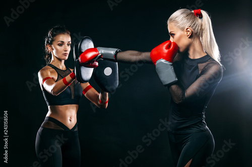 267c1098f Two women athlete and boxer trainging before fight on black background.  Sport and boxing concept