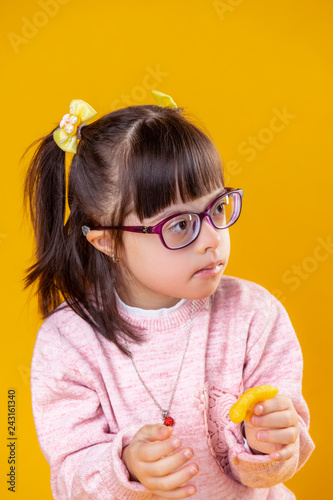 Valokuva  Dark-haired girl with down syndrome carrying orange chips