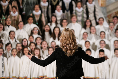 Photo Back of a woman conducting a choir of children