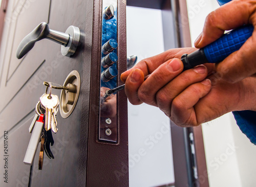 Fototapeta Handyman repairs the door lock obraz
