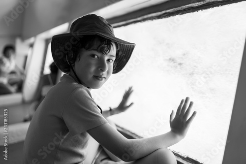 Fotografía  The boy is watching the underwater world through the large porthole below of  the waterline a tourist ship