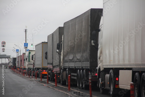 Платно Truck inspection - a long congestion traffic of many trucks with semi trailers convoy on weight control point