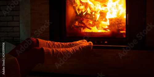 Fotografía A woman in knitted socks is sitting near the fireplace on a cold winter evening