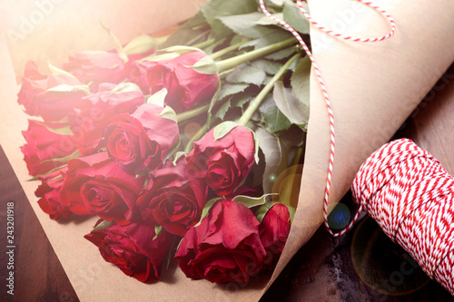 Fotografia, Obraz  Wrapping Valentine's Day red roses in brown paper on dark wood background with lens flare